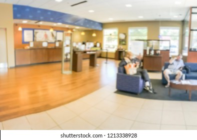 Blurred image male electrician on stepladder installing light on ceiling at bank branch office in America. Customer waiting at lobby couches, panorama view