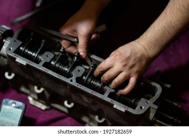 blurred image, male hands adjusting valve clearances on the cylinder head. cylinder head repair.