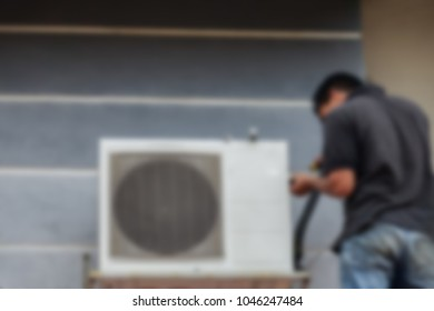 Blurred image of a  man repairing the  Air Conditioning System