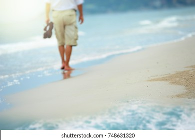 Blurred image of a man walking on the beach.
