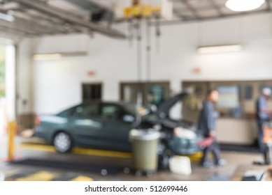 Blurred image mechanic changing oil of car at auto shop in Little Rock, Arkansas, US. Defocused background interior of modern oil change service station. Working technician at auto repair concept.
