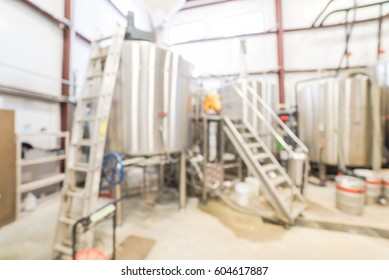 Blurred image modern beer plant (brewery) with stainless steel brewing equipment of kettle, vessel, tub, pipe. Row of large metal tanks in microbrewery. Brewery production vats, fermentation interior.