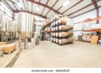 Blurred image modern beer plant (brewery) with stainless steel brewing equipments and stack of barrels in cellar. Row large metal tanks in microbrewery. Brewery production vats, fermentation interior.