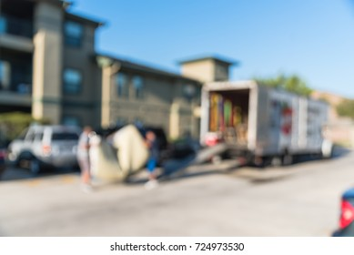 Blurred image mover carries mattress on loading ramp of moving truck for apartment relocation in Humble, Texas, USA. Relocate condominiums, homes, re-arranging furniture concept background.