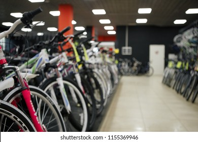 Blurred image multiple rows of kid bikes hanging on rack at department store in Humble, Texas, US. Various bright color bicycles for kid in bike shop. Active lifestyle concept background, vintage tone