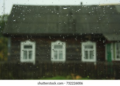 Blurred image of an old wooden house - view through a glass with raindrops