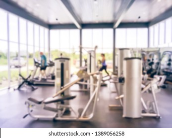 Blurred image of open space fitness center at new master‐planned community in Texas, America.  Cardio machines, weight, strength training equipment. Large glass wall with natural lights