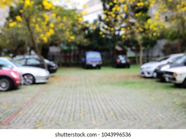 Blurred image of outdoor parking lot with yellow trumpet trees