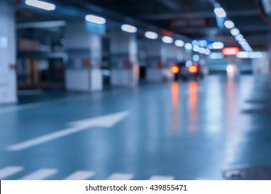 Blurred image/ Parking garage - interior shot of multi-story car park, underground parking with cars.