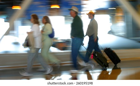 blurred image of passengers in transit at an airport