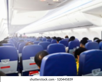 blurred image of people in the airplane cabin , in economy class