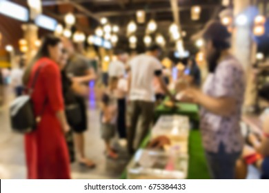 blurred image of people at the animals show in the night street market