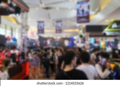 Blurred image of people attending indoor hall exhibition.
