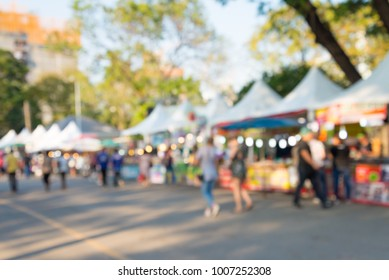 Blurred image of people in day market festival in city park background