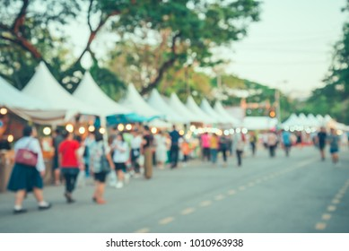 Blurred image of people in day market festival in city park background - vintage tone