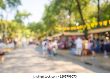 Blurred image of people in day market festival in city park background. Summer festival holiday or celebration concept.
