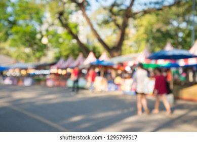 Blurred image of people in day market festival in city park background. Colorful outdoor food tent with lighting decoration. Summer festival holiday or celebration concept.
