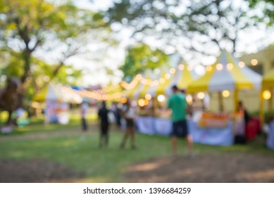 Blurred image of people in day market festival in city park background. Colorful outdoor food tent with lighting decoration. Summer festival holiday or celebration party concept.