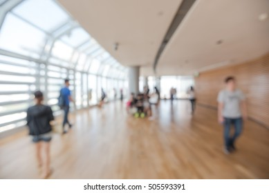 Blurred image people enjoying sightseeing from a modern observation desk of skyscraper in Singapore. Abstract background of people walking, seating and standing at huge observatory high-rise building.