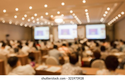 Blurred image of people in hall or auditorium with screen and bokeh light