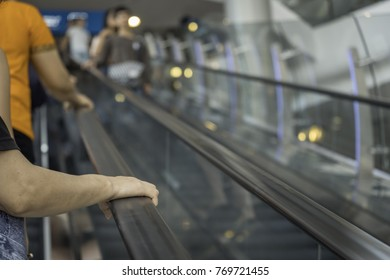 Blurred image of people holding on handrail when ascending escalator in shopping mall