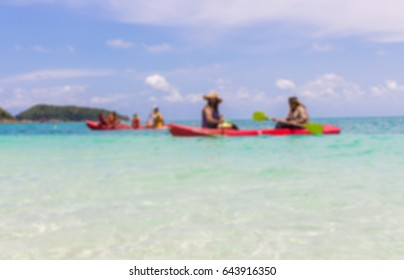 blurred image of people kayaking in the clear blue sea