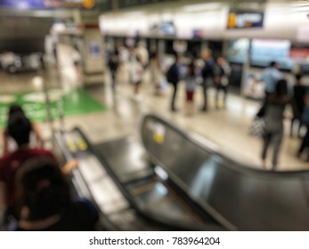 Blurred image of people on the escalator for go down in public subway train platform with passenger waiting for train coming. Blur background for design