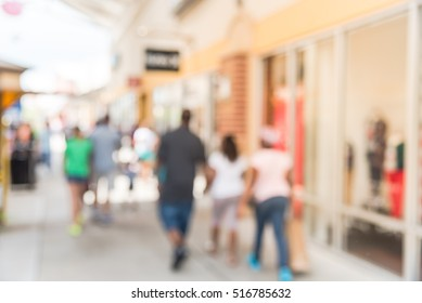 Blurred image of people out shopping at pedestrian outdoor courtyards and covered walkways in outlet mall in Houston, Texas, US. Wide range of retailers of designer apparel, jewelry, fine leather.