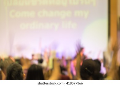 Blurred image of people raising hands to worship in adoration in revival concert.