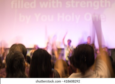 Blurred image of people raising hands in surrendering gesture for religion background