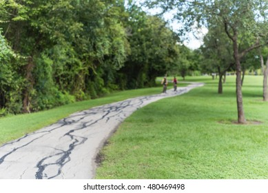 Blurred image people riding bicycle through s-curve path with green trees and grass in city park at Houston, Texas, US. Blurred cyclist pedals in outdoor exercise. Healthy lifestyle in summer concept.