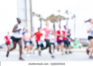 Blurred image of people running in massive marathon on a sunny summer day. Healthy living, workout and sports concept.