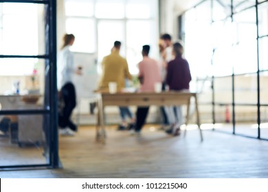 Blurred image, people silhouette collaborating in office interior. Defocused space for your information, teamwork process. Group of coworkers discussing ideas. Colleagues having informal work meeting