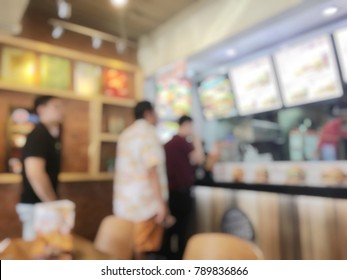 blurred image of People waiting and queuing  for order some food and make payment in Fastfood Store. vintage tone and light effect.