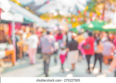 Blurred image of people walking at day market  in sunny day, blur background with bokeh
