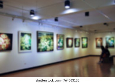 Blurred image of people watch painting in a gallery