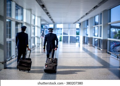 Blurred image of pilots walking at the airport terminal