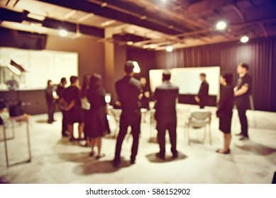 blurred image of production team is meeting, sitting and standing in production studio, the chairman is talking with the business project in television studio station.