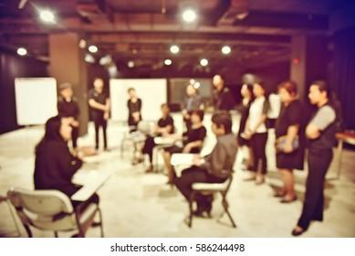 Unscharfes Bild des Produktionsteams sitzt und steht, der Vorsitzende spricht mit dem Business-Projekt im Fernsehstudio-Sender. Vintage-Filterfarbe