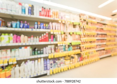Blurred image rows of hair care, skin care,  cosmetic, sunscreen and lotion sprays products on display at pharmacy store in US.