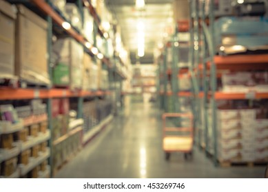 Blurred image of shelf in modern distribution warehouse or storehouse. Defocused background of industrial warehouse interior aisle. inventory, hypermarket,wholesale concept, bokeh light.Vintage filter
