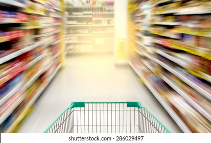 blurred image of shopping in supermarket with shopping cart