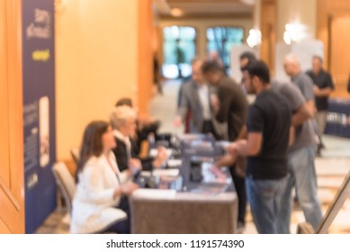 Blurred image side view diverse participants at registration check-in workshop table. Multiethnic people sign-up at conference hotel lobby and received instruction, event package from support staff