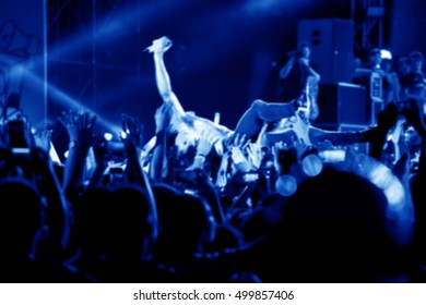 Blurred image of singer on top crowd surfing at a music concert
