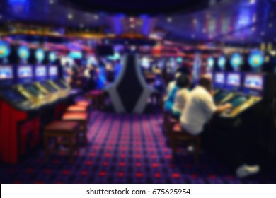 Blurred image of slots machines at the Casino games. people playing casino games