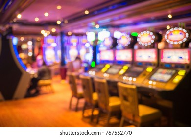 Blurred image of slots machines at the Cruise liner. people playing casino games in yellow tones