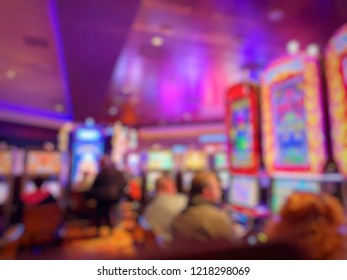 Blurred image of slots machines and people playing casino games at the Casino.