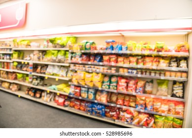 Blurred image of snacks and canned chips aisle in store at Humble, Texas, US. Wide perspective view shelves variety of snacks, defocused blurry background bokeh light in supermarket. Business concept.
