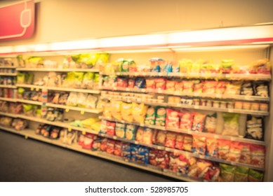 Blurred image of snacks and canned chips aisle in store at Humble, Texas, US. Wide perspective view shelves variety snacks, defocused background bokeh in supermarket. Business concept. Vintage tone.
