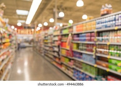 Blurred image of soda and cracker/chips aisle in store. Wide perspective view of empty store aisle and shelves, defocused blurry background with bokeh light in store. Business concept.